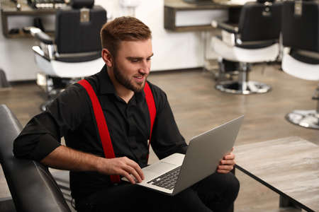 Young business owner working with laptop in barber shop