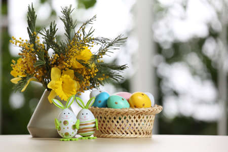 Festive composition with Easter eggs on table against blurred window, space for text