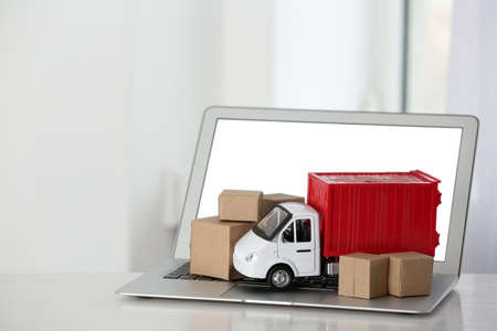 Laptop and truck model with boxes on table indoors. Courier service