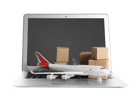 Laptop, airplane model and carton boxes on white background. Courier service