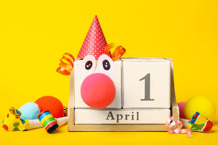 Wooden block calendar with clown face and party decor on yellow background. April fool's day