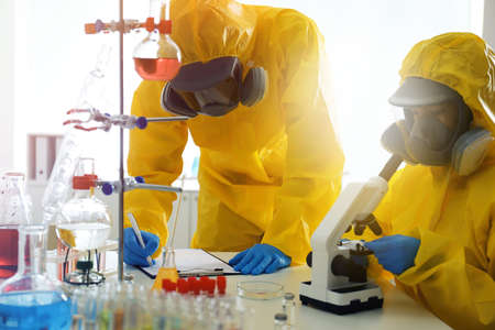Scientists in chemical protective suits working at laboratory. Virus research 스톡 콘텐츠