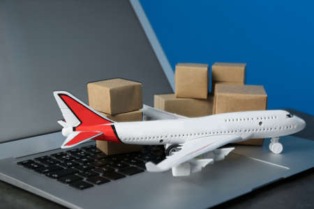 Laptop, airplane model and carton boxes on grey stone table, closeup. Courier service