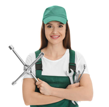 Portrait of professional auto mechanic with wrenches on white background