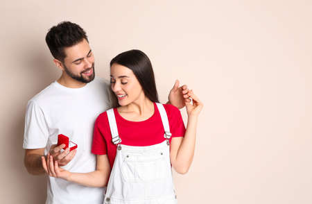 Man with engagement ring making marriage proposal to girlfriend on beige background Archivio Fotografico