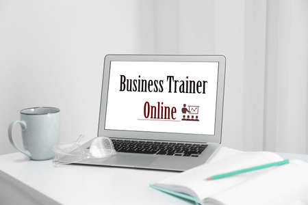 Modern laptop with text BUSINESS TRAINER ONLINE on desk indoors