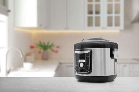 Modern electric multi cooker on table in kitchen. Space for design