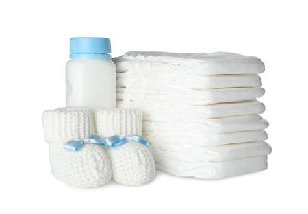 Disposable diapers, child's booties and bottle on white background