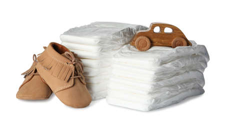 Disposable diapers, toy car and child's shoes on white background