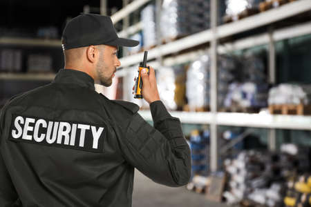 Security guard using portable radio transmitter in wholesale warehouse, space for text Stock fotó