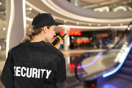 Security guard using portable radio transmitter in modern shopping mall, space for text Stock fotó
