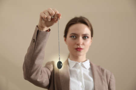 Psychotherapist with pendulum on beige background. Hypnotherapy session Banque d'images