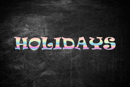 Word HOLIDAYS on black background. School's out