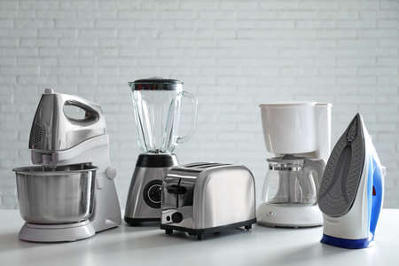 Set of modern home appliances on white table