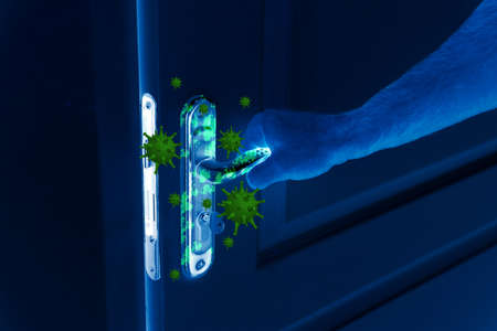 Man opening door, closeup view under UV light. Avoid touching surfaces in public spaces during coronavirus outbreak