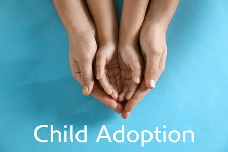 Mother holding hands with her child on blue background, top view. Adoption concept