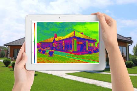 Frau erkennt Wärmeverlust im Haus mit Wärmebildanzeige auf Tablet im Freien. Energieeffizienz