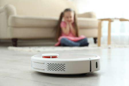 Little girl using robotic vacuum cleaner at home Banco de Imagens