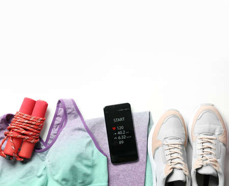 Smartphone with fitness app and sport accessories on white background, flat lay. Space for text