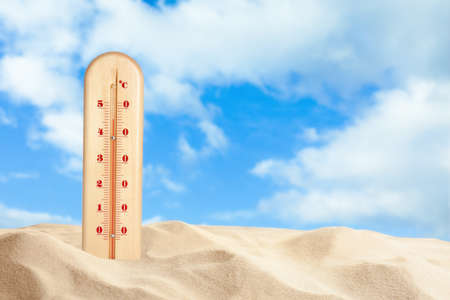 Weather thermometer with high temperature and sandy beach on sunny day