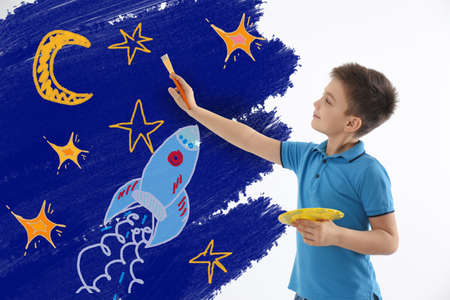 Cute child drawing space on white wall indoors Imagens