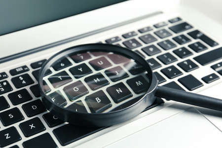 Magnifying glass on keyboard of modern laptop, closeup. Search concept