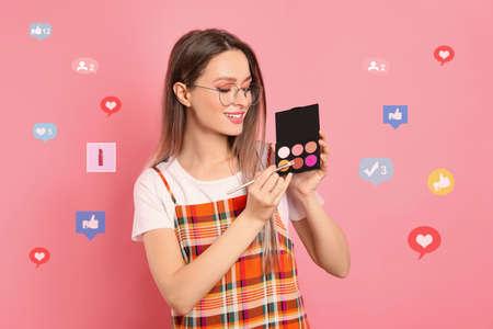Blogger de belleza con paleta de pincel y sombra de ojos sobre fondo rosa
