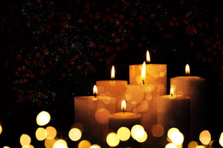 Burning candles on dark background, bokeh effect