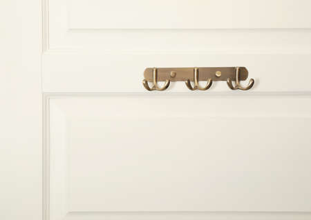 White door with empty metal clothes hooks Banque d'images