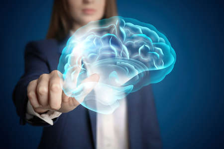Young woman pointing at digital image of brain on blue background, closeup Banque d'images - 145227494