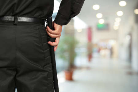 Security guard in uniform with police baton in shopping mall, closeup. Space for text