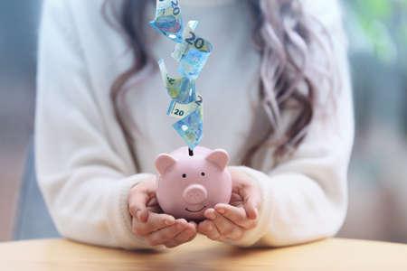 Woman with piggy bank at table indoors, closeup