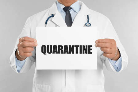 Doctor holding sign with text QUARANTINE on light grey background, closeup. Stay at home during coronavirus outbreak