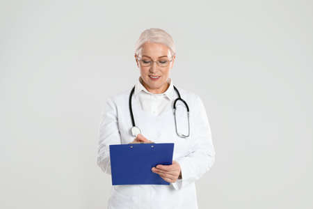 Mature doctor with clipboard on light grey background