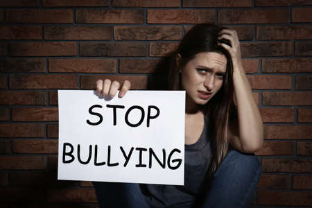 Abused teen girl with sign STOP BULLYING near brick wall 写真素材