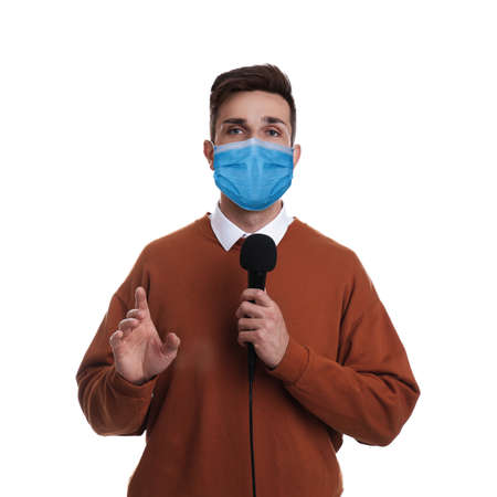 Male journalist with microphone wearing medical mask on white background. Virus protection