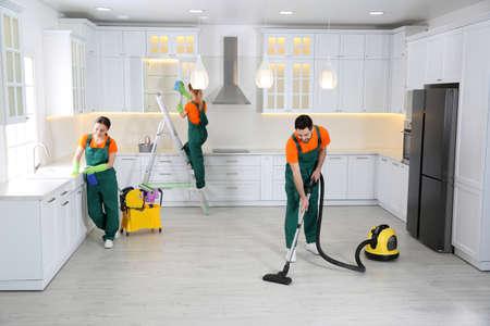 Équipe de concierges professionnels nettoyant la cuisine moderne Banque d'images