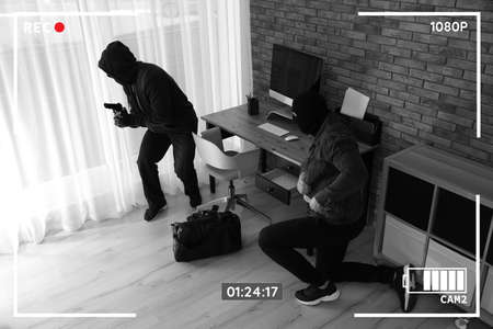 Dangerous masked criminals with weapon stealing money from house, view through CCTV camera