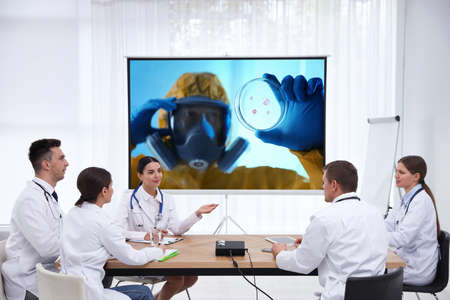 Team of doctors using video projector during coronavirus conference in office