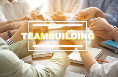People holding hands together at table. Teambuilding concept