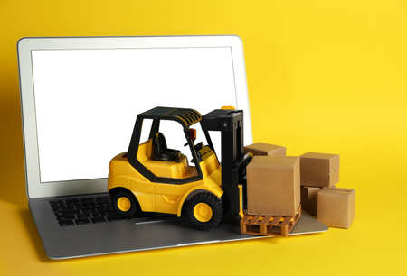 Laptop, forklift model and carton boxes on yellow background. Courier service Imagens