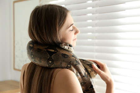 Young woman with boa constrictor at home. Exotic pet