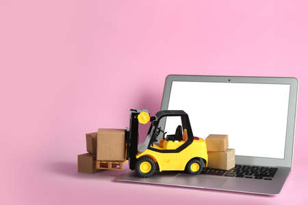 Laptop, forklift model and carton boxes on pink background. Courier service