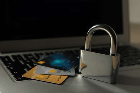Credit cards, lock and laptop on table, closeup. Cyber crime Stok Fotoğraf