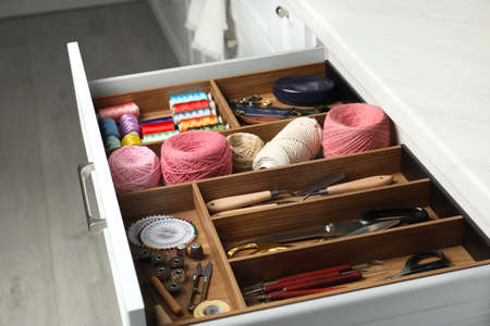 Sewing accessories in open desk drawer indoors