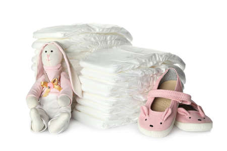 Disposable diapers, toy bunny and child's shoes on white background Banque d'images