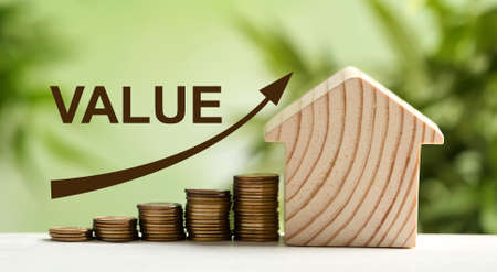 Model of house and stacked coins on table against blurred green background. Growing value
