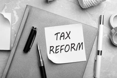 Reminder note with words TAX REFORM and stationery on table, flat lay