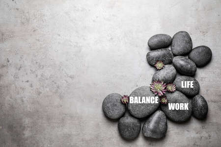 Work-life balance concept. Stones and flowers on grey background, flat lay with space for text