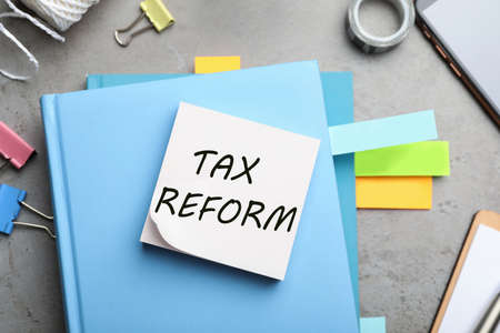 Reminder note with words TAX REFORM and stationery on table, flat lay 版權商用圖片